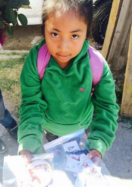 Natalie Velazquez holds a small packet with pope memorabilia. (Maria Esquinca)