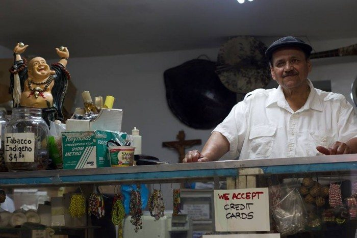 "Jorge ""Justo"" Vargas behind the counter of his iconic botánica in Spanish Harlem (Photo Credit: Andrew J. Padilla)"